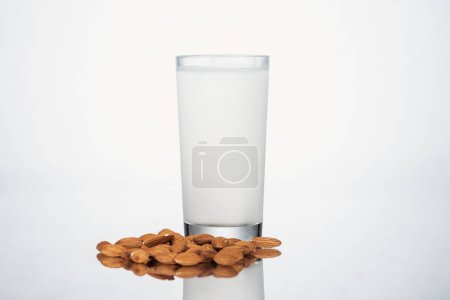Photo for Almond vegan milk in glass nuts on grey background - Royalty Free Image