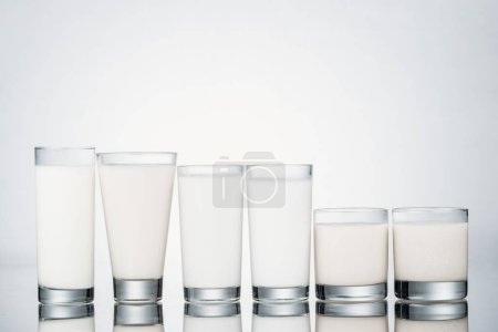 Photo for Row of glasses with organic vegan milk on grey background - Royalty Free Image
