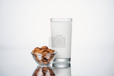 Photo for Almond vegan milk in glass near bowl with nuts on grey background - Royalty Free Image