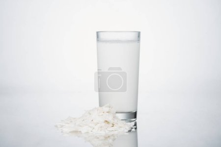 Photo for Coconut vegan milk in glass near coconut slices on grey background - Royalty Free Image