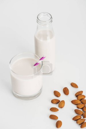 Photo for Organic almond milk in bottle and glass with straw near scattered almonds - Royalty Free Image