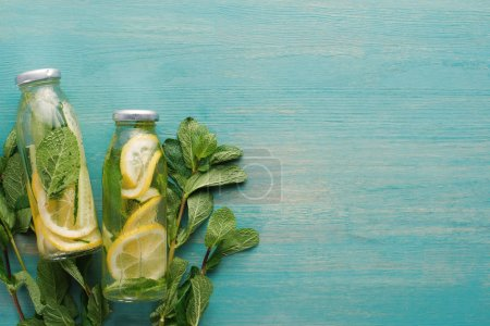 Photo for Top view of detox drink in bottles with lemon and cucumber slices and mint on blue wooden surface - Royalty Free Image