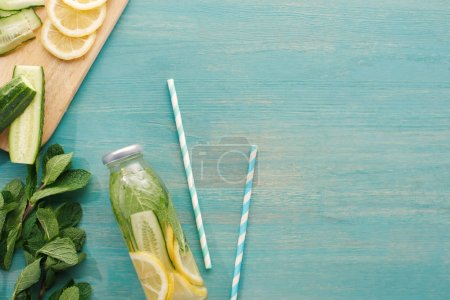 Photo for Top view of detox drink in bottle near lemon and cucumber slices, mint and straws - Royalty Free Image