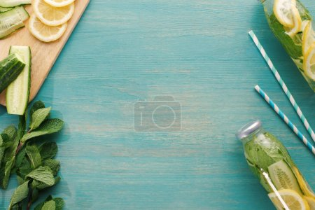 Photo for Top view of detox drink in bottles near lemon and cucumber slices, mint and straws - Royalty Free Image