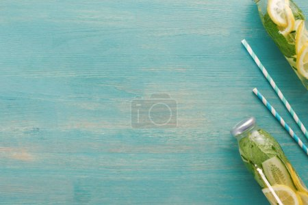 Photo for Top view of detox drink with lemon, mint and cucumber in bottles near straws - Royalty Free Image