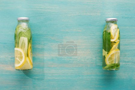 Photo for Top view of detox drink in bottles with fresh lemon and cucumber slices and mint - Royalty Free Image