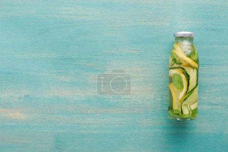 Photo for Top view of detox drink in bottle with fresh lemon and cucumber slices and mint - Royalty Free Image