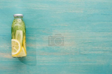Photo for Top view of detox drink in bottle with fresh lemon and cucumber slices and green mint - Royalty Free Image