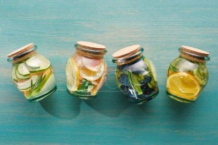 Photo pour Vue de dessus de boissons détox dans des pots avec des agrumes sur la surface en bois bleue - image libre de droit