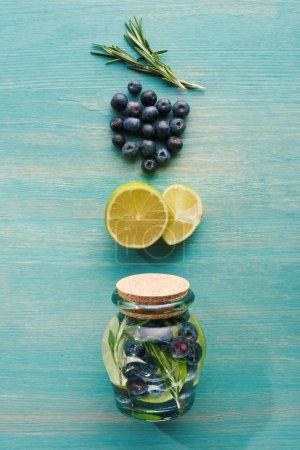 Photo pour Vue du dessus de boisson de désintoxication dans un bocal avec citrons, romarin et myrtilles - image libre de droit