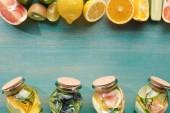"""Постер, картина, фотообои """"вид сверху Детокс напитки в банках с фруктами, овощами, травами, ягодами и зеленью вблизи ингредиентов на деревянной синей поверхности"""""""