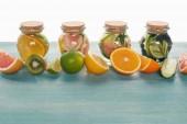 """Постер, картина, фотообои """"Детокс напитки в банках с фруктами, овощами, зеленью, ягодами и зеленью возле ингредиентов на деревянной синей поверхности, изолированной на белом"""""""