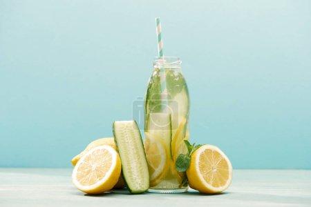 Foto de Bebida Detox en botella con paja cerca de limones, menta y pepino aislado en azul - Imagen libre de derechos