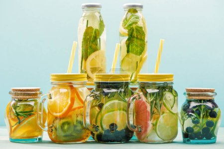 organic detox drinks with berries, fruits and vegetables in jars and bottles with straws isolated on blue