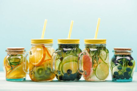 Photo for Fresh detox drinks with berries, fruits and vegetables in jars with straws isolated on blue - Royalty Free Image