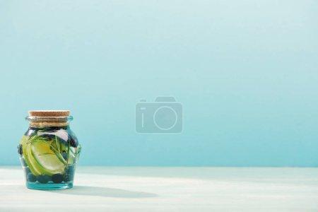 Photo pour Boisson de désintoxication dans un bocal avec romarin, bleuets, citrons verts isolés sur bleu - image libre de droit