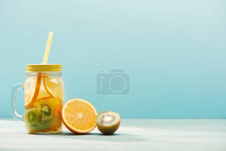 Photo for Detox drink in jar with straw near orange and kiwi isolated on blue - Royalty Free Image