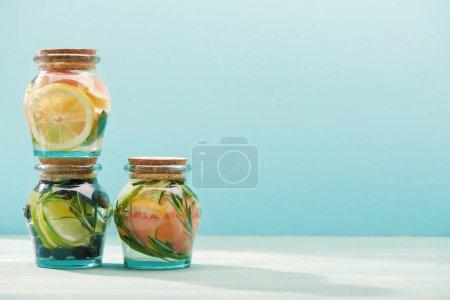 Photo pour Boissons détox dans des pots avec des fruits frais isolés sur le bleu - image libre de droit