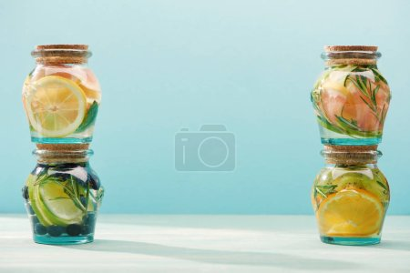 Photo for Detox beverages in jars with fresh fruits isolated on blue - Royalty Free Image