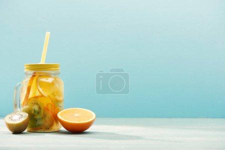 Bio-Entgiftungsgetränk im Glas mit Stroh in der Nähe von Orange und Kiwi isoliert auf blau