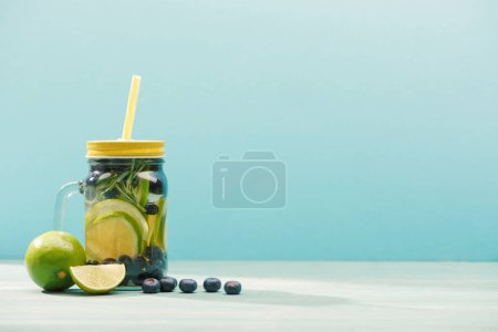 Photo for Fresh detox drink in jar with straw near blueberries and limes isolated on blue - Royalty Free Image