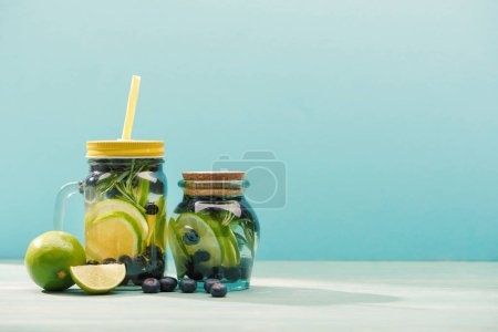 Photo for Fresh detox drinks in jars near blueberries and limes isolated on blue - Royalty Free Image