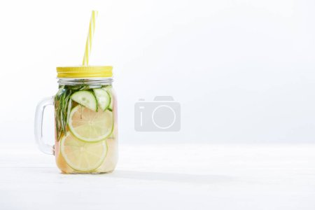 Photo for Fresh detox drink in jar with limes, cucumbers, rosemary and grapefruit on white background - Royalty Free Image