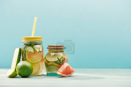 Photo for Fresh detox drinks in jars near limes, cucumber and grapefruit isolated on blue - Royalty Free Image