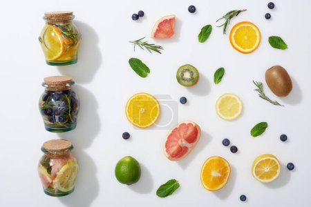 Photo for Top view of detox drinks in jars near fruit slices, blueberries, mint and rosemary - Royalty Free Image