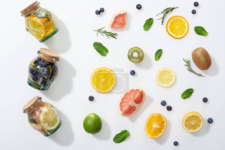 top view of detox drinks in jars near fruit slices, blueberries and herbs