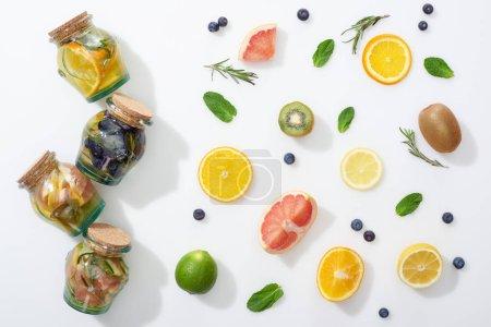 Photo pour Vue de dessus de boissons détox dans des pots près des tranches de fruits, baies, menthe et romarin - image libre de droit