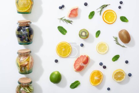 Photo for Top view of detox drinks in jars near fruit slices, berries and herbs - Royalty Free Image
