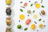 """Постер, картина, фотообои """"вид сверху Детокс напитки в банках вблизи фруктовые ломтики, ягоды и травы"""""""