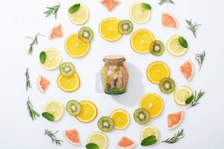 Photo for Flat lay with fresh sliced kiwi, oranges, lemons, grapefruits, mint, rosemary and detox drink in jar - Royalty Free Image