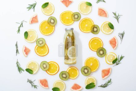 Photo for Flat lay with sliced kiwi, oranges, lemons, grapefruits, mint, rosemary and detox beverage in bottle on grey background - Royalty Free Image
