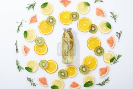 Photo for Flat lay with sliced kiwi, oranges, lemons, grapefruits, mint, rosemary and detox drink in bottle on grey background - Royalty Free Image