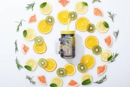 Foto de Plana con kiwi en rodajas, naranjas, limones, pomelos, menta, Romero y bebida Detox en frasco sobre fondo gris - Imagen libre de derechos