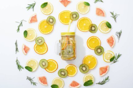 Photo for Flat lay with sliced kiwi, oranges, lemons, grapefruits, mint, rosemary and detox drink in jar with straw on grey background - Royalty Free Image