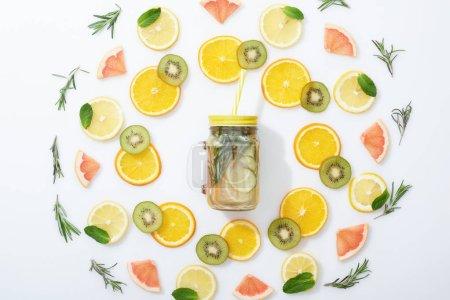 Foto de Plana con kiwi en rodajas, naranjas, limones, pomelos, menta, Romero y bebida Detox en tarro sobre fondo gris - Imagen libre de derechos