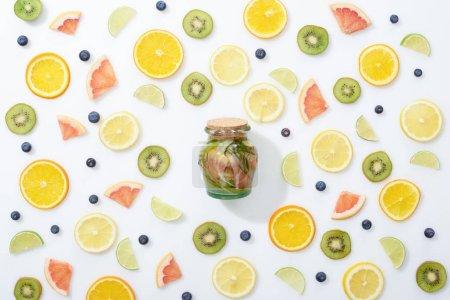 Foto de Vista superior de la bebida Detox en tarro entre frutas en rodajas y arándanos sobre fondo blanco - Imagen libre de derechos