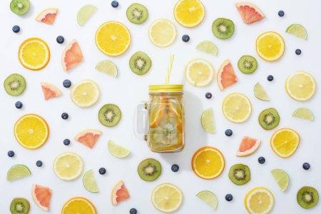 Foto de Vista superior de la bebida Detox en tarro entre frutas y arándanos sobre fondo blanco - Imagen libre de derechos