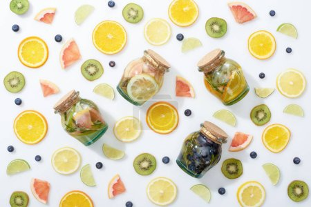 top view of detox drinks in jars among sliced fresh fruits and blueberries on white background