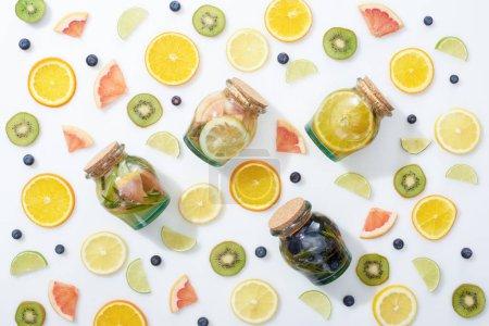 Foto de Vista superior de bebidas Detox en frascos entre frutas y arándanos sobre fondo blanco - Imagen libre de derechos