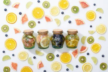 Photo for Top view of detox drinks in jars among sliced fruits and blueberries on white background - Royalty Free Image