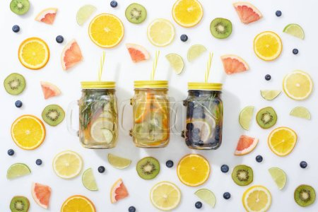 Photo for Top view of detox drinks in jars with straws among sliced fruits and blueberries on white background - Royalty Free Image