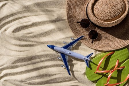 Photo for Top view of toy plane, straw hat, flip flops and sunglasses on wavy sand with copy space - Royalty Free Image