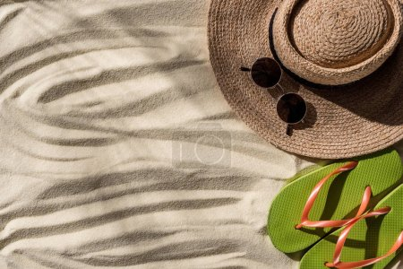 Photo for Top view of straw hat, flip flops and sunglasses on wavy sand with copy space - Royalty Free Image