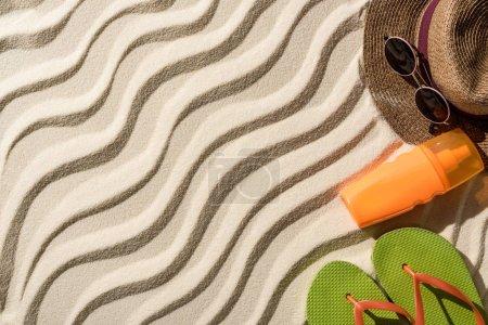 Foto de Vista superior de sombrero de paja, chanclas, bloqueador solar y gafas de sol en arena ondulada con espacio de copia - Imagen libre de derechos