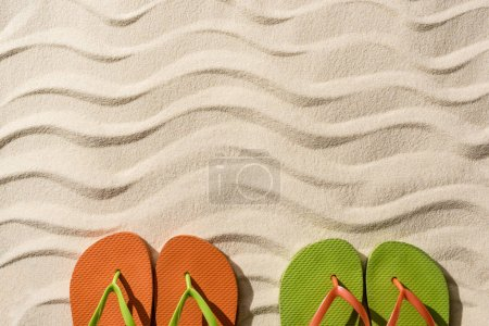 Photo for Top view of colorful flip flops on wavy sand with copy space - Royalty Free Image