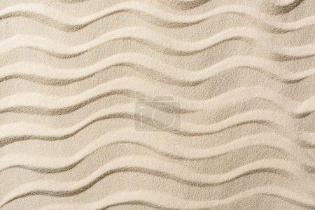 Draufsicht auf strukturierten Hintergrund mit Sand und sanften Wellen
